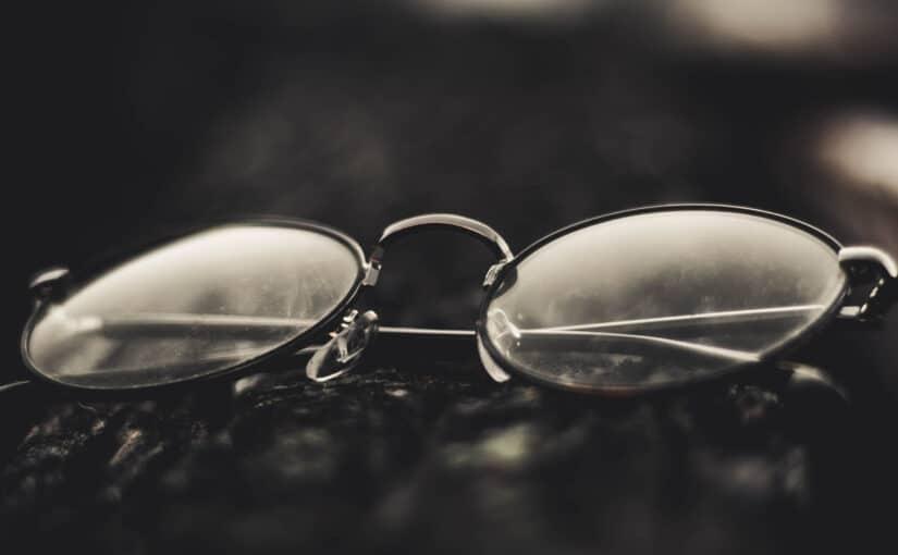 Brille mit runden Gläsern liegt auf einem Tisch
